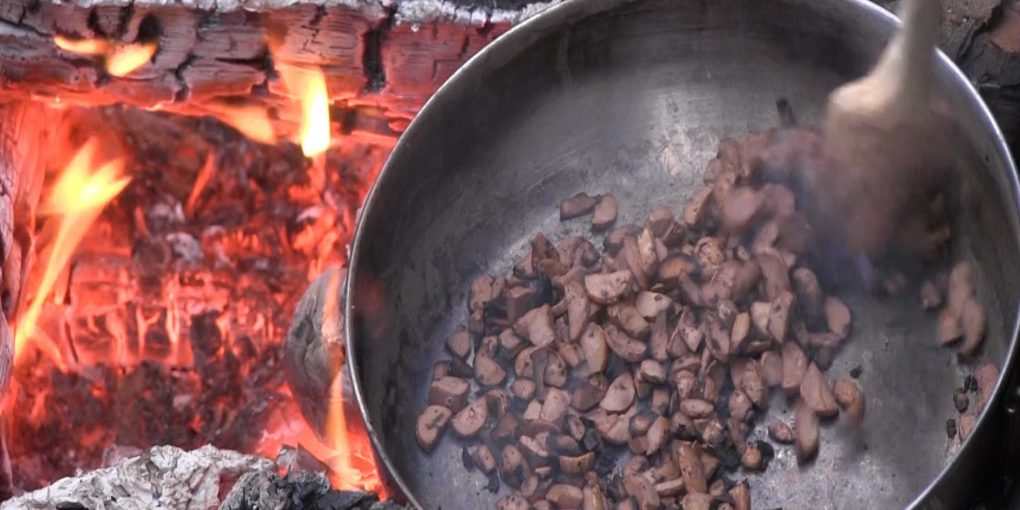 acorns in skillet roasting over an open fire